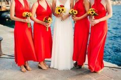Brautjungfern in den roten Kleidern, in den Handblumensträußen von Sonnenblumen wed Lizenzfreie Stockfotografie