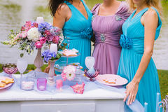 Brautjungfern umarmen nahe der festlichen Tabelle an der Zeremonie Hochzeitsdekoration im Stil des boho, mit Blumen Lizenzfreie Stockfotos