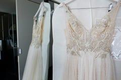 Brautkleider, die an einem Aufhänger hängen stockbilder