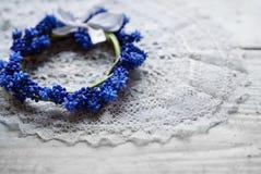 Brautkranz, der auf einer Spitzeserviette liegt Braut im weißen Kleid Blaue Blumen Lizenzfreies Stockfoto
