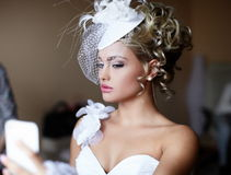 Brautmädchen im Hochzeitskleid, das im Spiegel schaut Lizenzfreie Stockfotografie
