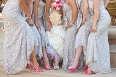 Brautmädchen mit der Braut, die Blumensträuße anhält Stockbilder