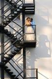 Brautpaare, die auf einem Treppenhaus küssen Stockbild
