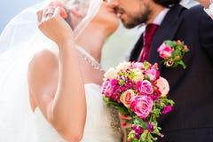Brautpaare, die unter Schleier an der Hochzeit küssen Lizenzfreie Stockfotos