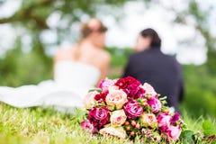 Brautpaare mit dem Blumenstrauß, der auf Wiese sitzt Lizenzfreies Stockfoto