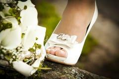 Brautschuh mit Blumenstrauß Stockfotos