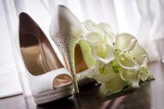 Brautschuhe und Blumenstrauß Stockbild