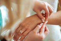 Brautvorbereitung, Braut, die auf Schmuck, Fokus auf Armband sich setzt Lizenzfreie Stockbilder