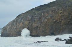 Brave волны ломая против утесов где обитель Сан-Хуана De Gaztelugatxe Is обнаружила местонахождение здесь игру снятых тронов арби стоковое изображение