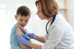 Brave boy receiving injection or vaccine with a smile. Brave child boy receiving injection or vaccine with a smile stock photo
