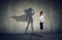 Brave business woman posing as super hero. Side view of a business woman imagining to be a super hero looking aspired royalty free stock photo
