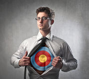 Brave businessman. Young businessman showing a target on his chest under his shirt Stock Image