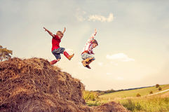 Brave, carefree boys jump  hay. Two little boys in cowboy boots, having fun on a farm,  jumping in the hay. I wanna fly Royalty Free Stock Photo