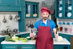 Brave chef with spoons in hands in red apron and red cap. Guy in hat and apron standing on kitchen in front of table with vegetables. Hell kitchen and brave Stock Images