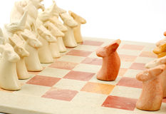 Brave chess pawn. A brave lone pawn making the first move in a chess match depicting the act of a brave soldier. Photo taken on a hand carved stone chess set Stock Photos