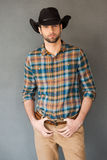 Brave cowboy. Handsome young man wearing cowboy hat and looking at camera while standing against grey background Royalty Free Stock Image