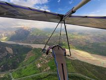 Brave extreme hang glider pilot flies high over valley with rive Royalty Free Stock Photo