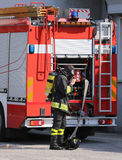 brave firefighters with fire engine truck during an exercise Royalty Free Stock Photos