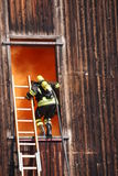Brave firefighters with oxygen cylinder goes into a house through a window during a fire stock photo
