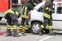 Brave firefighters relieve an injured after a road accident Royalty Free Stock Image