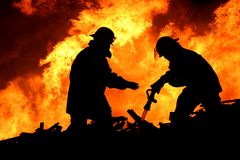 Brave Firefighters in Silhouette Stock Image