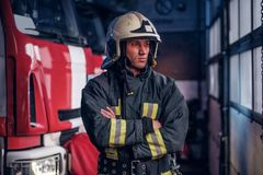Fireman wearing protective uniform standing next to a fire engine in a garage of a fire department, crossed arms and. A brave fireman wearing protective uniform royalty free stock photos