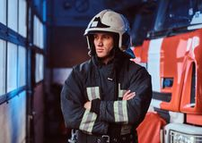 Fireman wearing protective uniform standing next to a fire engine in a garage of a fire department, crossed arms and royalty free stock photos