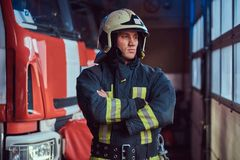 Fireman wearing protective uniform standing next to a fire engine in a garage of a fire department, crossed arms and royalty free stock photo