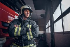 Fireman wearing protective uniform standing next to a fire engine in a garage of a fire department, crossed arms and. A brave fireman wearing protective uniform royalty free stock photo