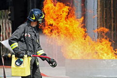 Brave fireman who puts out the fire with a fire ex Royalty Free Stock Photo