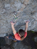 Brave girl climbs up on the dangerous rocks. Stock Photos