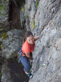 Brave girl climbs up on the dangerous rocks. Royalty Free Stock Photos