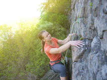 Brave girl climbs up on the dangerous rocks. Royalty Free Stock Images