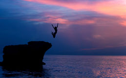 Brave girl jumping from rocks. Brave girl jumping from the rocks in the evening on beautiful purple sunset background, summer adventure, freedom concept Royalty Free Stock Photos