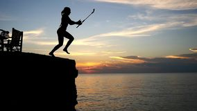 Brave girl jumping into the sea from a rock with go pro action camera during beautiful sunset. slow motion. 1920x1080. Brave girl silhouette jumping into the sea stock video footage