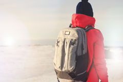 Brave girl traveler with a backpack and in winter clothes looking ahead. Lens flare effect Royalty Free Stock Photo