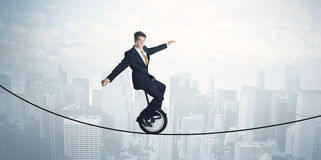 Brave guy riding a monocycle on a rope above cityscape Royalty Free Stock Photo