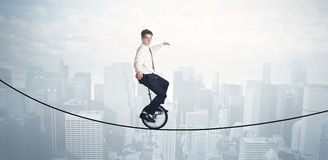 Brave guy riding a monocycle on a rope above cityscape Royalty Free Stock Photography