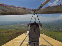 Brave hang glider pilot runs on wooden ramp for take off. Royalty Free Stock Photo