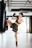 Brave kickboxer showing position of high kick indoors. Sticking with leg Stock Photography