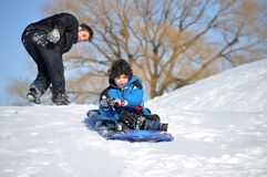 Little Latin Child Sliding Down on a Snowy Steep H. A brave Hispanic kid slides down on his own on a steep snowy hill in a chilly winter day, having fun in the Stock Photos