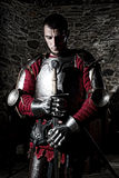 Brave Knight Standing With Head Bowed In Prayer And Holding Metal Sword Against Stone Wall Stock Photos