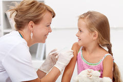 Brave little girl receiving injection. Or vaccine with a smile stock photos