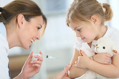 Brave little girl receiving injection by doctor Stock Images