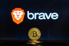 Brave logo on a computer screen with a stack of Bitcoin cryptocurency coins. Bitcoin coins with Brave browser logo on a laptop screen. Cryptocurrency and royalty free stock images