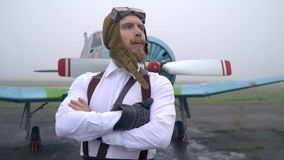 A strong pilot in a 60th suit stands in a brave pose in front of a plane with a propeller and looks into the distance stock video