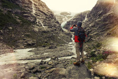 Brave man with a backpack, photographs glacier and mountain landscape on a smartphone Stock Images