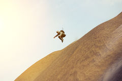 Brave man with backpack running and jumping on a dune. In the desert Royalty Free Stock Photo