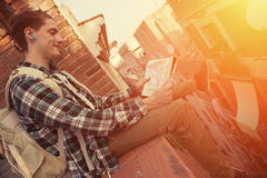 Brave man with backpack sitting on the edge of high roof with map in hands. Young and brave man with backpack sitting on the edge of high roof with map in hands Royalty Free Stock Photos