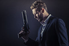 Brave man with dangerous weapon. Brave cool man holding a dangerous weapon on dark background royalty free stock photo